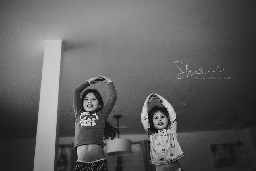 Sisters dancing with arms in the air, photographed by a Long Island Family Photographer