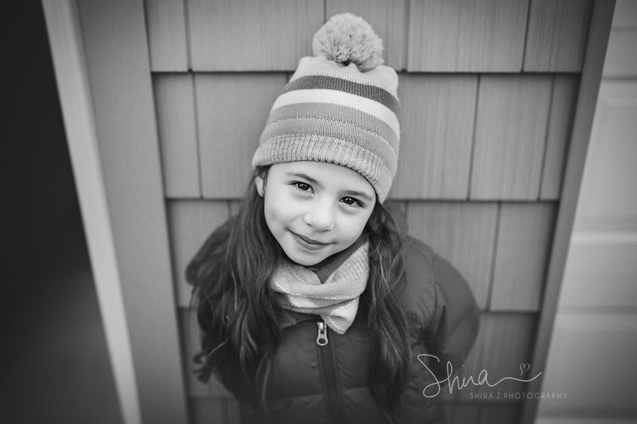 Six year old girl wearing a winter hat and scarf smiling for a Long Island Family Photographer
