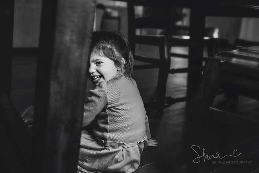 3 year old girl smiling under table at Long Island Family Photography
