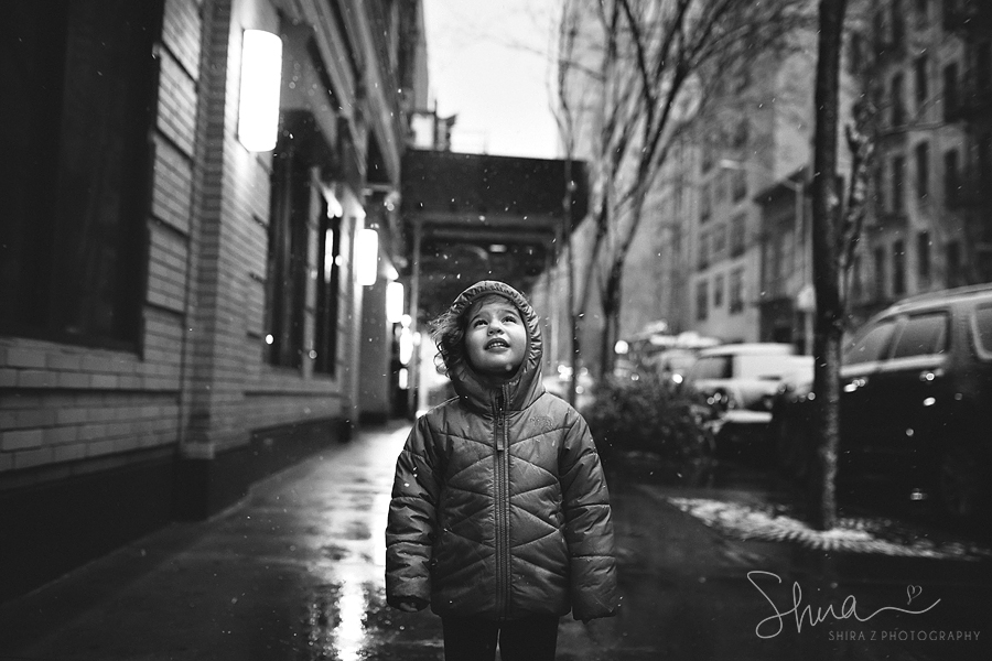 Photograph of a little girl standing in NYC with snow falling down