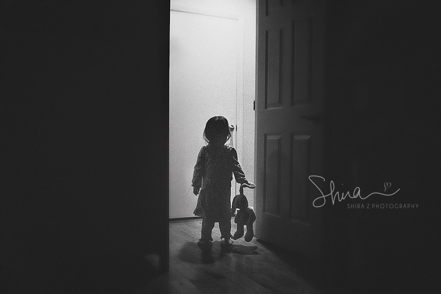 little girl getting ready for bed holding her bunny in shadow in Long Island, NY