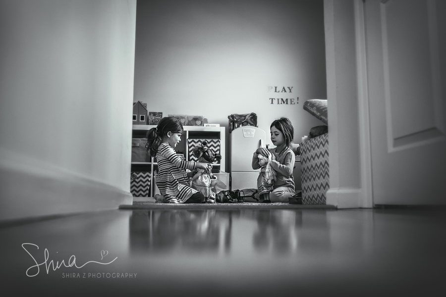 2 sisters playing with dolls in play room Long Island, NY