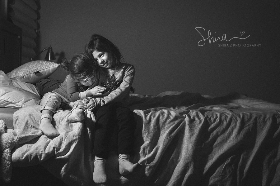 Black and White photo of sisters on a bed leaning on each other photographed by Long Island Family Photographer